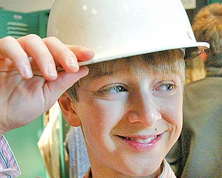 William D. Lewis/The Vindicator Chance Retino,a student at the University School in Shaker Hgts dons a hard hat during a recent tour of the Steel Museum. students from his school visit the museum each year.