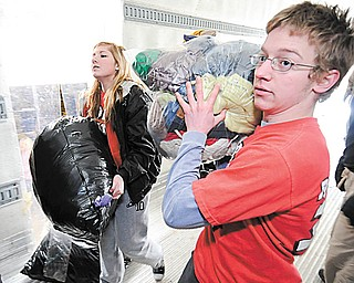 Girard 11th grader Abbie Hall (L) and Girard 12th grader Max Horne both members of Robo Cats help load a truck full of supplies for Haiti on Saturday as part of a Girard Liberty Rotary.   Photo/Mark Stahl