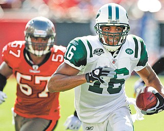 New York Jets wide receiver Brad Smith (16) outruns Tampa Bay Buccaneers linebacker Adam Hayward (57) for a first down on a wildcat play during the first quarter of an NFL football game Sunday, Dec. 13, 2009, in Tampa, Fla.