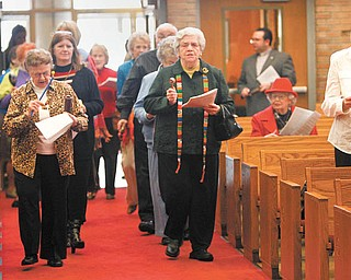 Participants for a World Day of Prayer service Thursday, wearing colorful scarves and animal-print clothing, play rattles, tambourines, shakers and bells as they walk up the aisle of Bethel Lutheran Church in Boardman. Leading are Joyce Rettenmeir, left,  and Ruth Abbott. Their apparel and instruments were a tribute to the women of Cameroon, Africa, who wrote the ecumenical service.