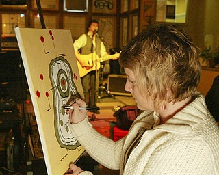 Artist Mary Farragher works on a painting while singer Simon Kenneally entertains at the Lemon Grove Café. The West Federal Street café serves up live music, local artwork, poetry readings, lecturers and discussion groups.