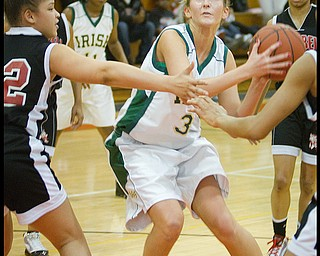Geoffrey Hauschild|The Vindicator.Ursuline's Allison Naples (31) makes her way to the hoop while being defended by Campbell's Naja Thomsas (32 left) and teamates during the second quarter at Mineral Ridge High School on Saturday afternoon.