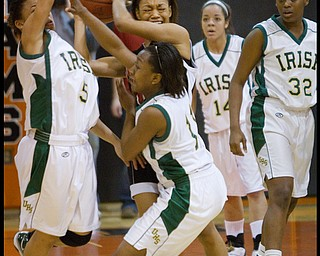 Geoffrey Hauschild|The Vindicator.Campbell's Brande Ellington (11) struggles to keep control of the ball while defended by Ursuline's Aurielle Irizarry (5) and Keneesha Tensley (11)  with their teamates, Ja'Nice Whitehead (14) and Courtney Powell (32) at right, during the fourth quarter at Mineral Ridge High School on Saturday afternoon.