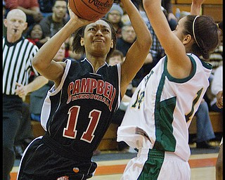 Geoffrey Hauschild|The Vindicator.Campbell's Brande Ellington (11) tries for a layup against Ursuline's Ja'Nice Whitehead (14) during the fourth quarter at Mineral Ridge High School on Saturday afternoon.