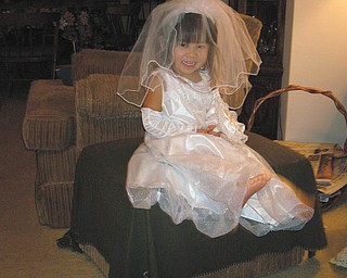 Jenni-Lin HuaYi Remias, granddaughter of Norma Remias of Canfield, is playing dress-up in her bridal outfit that was a Christmas present. She resembles the barefoot bride!