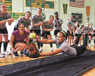 GIRL Magazine sponsored a visit by Olympic softball gold medalist Jessica Mendoza, second from left, to Ursuline High School on Tuesday. Mendoza spent the day talking to the Ursuline players about running, sliding, hitting, diving, bunting and other techniques to become a better softball player and athlete, as demonstrated by Ursuline player Malikka Cage, foreground. Cage initiated Mendoza's visit, writing to ESPN and inviting them to come to the school.