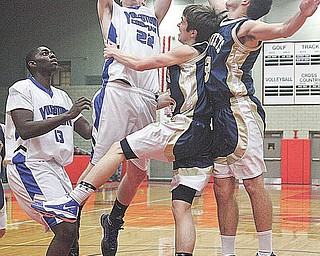 (22) Casey Carroll of Youngstown Christian goes strong to the rim as (15) Mike Mangine and (3) Pat Minnie play defense. (13) Anthony Walker watches the play during their game Tuesday night in Struthers.