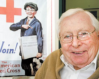 W. Russell Preston, executive director, Mahoning County Chapter of American Red Cross, says the local chapter remains active in helping people recover from disasters near and far. The chapter is celebrating its centennial this year. In the background is a vintage poster at the chapter's Boardman headquarters.