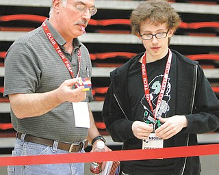 Marty Fernpack, left, committee member and judge, and Jarret Scacchetti, a Youngstown State University student, check the size of the block to be moved by robots.