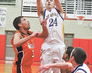 BOYS BBALL - (24) Matthias Tayala shoots over (33) Jalen DeSarro during their game Monday night in Struthers. - Special to The Vindicator/Nick Mays