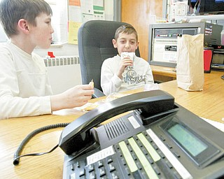 Lloyd Elementary third-graders Ethan Cochran, left, and Blake Kusky man the phones during their lunch period each day. Students in each of the Austintown School District buildings are chosen to help answer phones at their respective school. Ethan said it's one of the most sought-after student jobs at Lloyd.