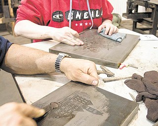Geoffrey Hauschild|The Vindicator. Show Room Supervisor, April Powell, of Grove City, uses an EDM Stone, or synethetic sanding stone, to remove debris and pockmarks from a rescued dye at Wendell August Forge's temporary workshop in Grove City on Monday afternoon.