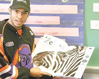 """Jordan Tibbett, a goalie for the Youngstown Phantoms, reads """"Life Size Zoo"""" to third-graders at Lloyd Elementary in Austintown. Tibbett, along with nine of his teammates, read to students in first, second and third grade Tuesday afternoon."""