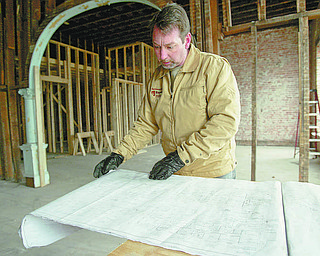 William D. Lewis|The Vindicator Paul Clouser, owner of National Fire Repair, looks over plans in an old building he is restoring on W.Market St in downtown Warren. The building will host National Fire Repair's offices on the first floor and  l apartments on the 2nd floor. Clouser is making an apartment on the3 rd floor for he and his wife.