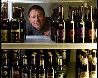 The Vindicator/Geoffrey Hauschild.President of Vintage Estate, Phil Reda, poses for a portait behind some of teh 760 beers at Vintage Estate along South Ave. on Tuesday afternoon.