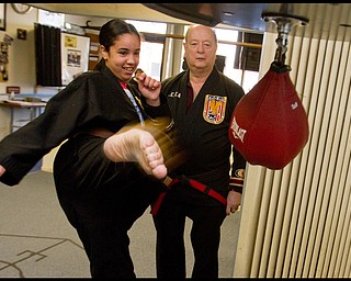The Vindicator/Geoffrey Hauschild.Heather Powell, 17 of Youngstown, kicks a bag alongside ?Todd? Vea during a karate lesson at AE Vea Karate along Belmont Ave. on Friday afternoon.
