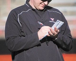 Head coach Eric Wolford makes notes during drills at YSU's recent spring football practice at Stambaugh Stadium. Wolford spent his first practice doing more observing than coaching.