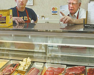 The Meating Place employee Ray Harnevious Jr., left, and store co-owner Tom Rochford discuss some of the most- popular cuts of meat sold at the Austintown butcher shop. Rochford, 74, said he and longtime friend Jack Weaver opened the store, which is stocked with a variety of chicken, beef, pork, fish and more, in 1982.