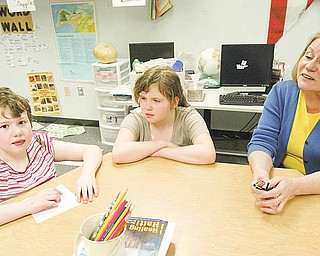 William D. Lewis| The Vindicator  Rich Center teacher Patty Fisher, right, works with students Morgan Kerr, 9, left, and Rebecca Miller, 10 at  the Rich Center at YSU 3-19-10.