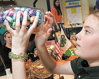 William D. Lewis| The Vindicator Sarah Veverka, 10, of Canfield and a member of the Greenford Busy Bees 4-H club tries to guess the number of chocolates in a jar during  4-H community Day at Lord of Life Luthern Church in Canfield Saturday 3-20-10.
