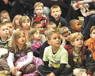 """Kindergarten students from Poland's elementary schools await Baby T. Rex, one of 17 life-size dinosaurs that will storm the Covelli Centre on May 4-5 at the """"Walking with Dinosaurs"""" show."""