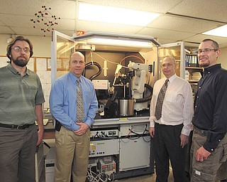 Officials stand near laboratory equipment at Youngstown State University that led Zethus Software of Youngstown to form a partnership with the German company that makes the equipment. Shown are Andre Reinhardt, Zethus co-founder, left; Brad Myers, Zethus chief executive; Allen Hunter, YSU chemistry professor; and Eric Parker, Zethus co-founder.
