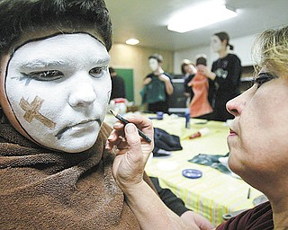 "Jacob Seink, 13, of Newton Falls waits patiently as his mother, Amy, applies his makeup for the spiritual mime ministry ""For You, For Me."" The traveling troupe, which involves from 15 to 20 seventh- and eighth-graders from Lake Milton, Newton Falls and North Jackson, is presenting the Passion of Christ at various sites."