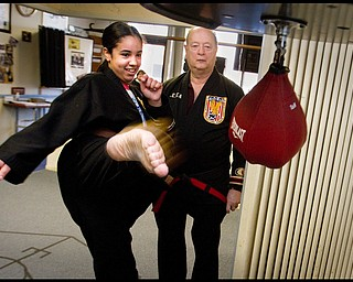The Vindicator/Geoffrey Hauschild2.19.2010Heather Powell, 17 of Youngstown, kicks a bag alongside instructor, Todd Vea, during a karate lesson at AE Vea Karate along Belmont Ave. in Youngstown on Friday afternoon.