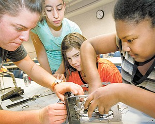 Second-year Youngstown State University civil engineering major Micelle Stipetich, from left, helps Liberty sixth-graders Haneen Kotb, 12, Jordyn Faustino, 11, and Teshaia Cain, 11, disassemble a toaster during Tear Apart A Toaster. The Thursday event at YSU's Moser Hall was arranged by the university's Society of Women Engineers. Stipetich helped organize the event.