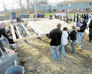 Habitat for Humanity volunteers move walls into place while working on a house on Maranatha Drive in Youngstown.