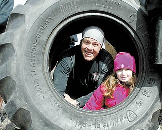 """Ironman Warehouse gym is moving from Wilson Ave to downtown Youngstown. Owners and friends carried logs, tires and and other workout equipment the 1.8 miles to the new location. Owner Paul """"Dunner"""" Dunleavy and his niece Jillian Dunleavy look out of one of the tires used for workouts at the gym."""