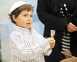 Dylan Shapiro, 5, holds a cup of grape juice, which is part of the order of the Seder. The ritual meal, which took place for Akiva Academy students, involves drinking four cups of grape juice or wine, which symbolize four of God's promises of freedom to the Jewish people. Wine is a symbol of joy.