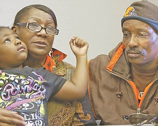 Wanda Greer holds her 5-year-old granddaughter, Amaya Greer, while seated next to her husband, Bill. The Greers' youngest son, Brian, was shot to death Monday on the North Side. Amaya is one of Brian's five children.
