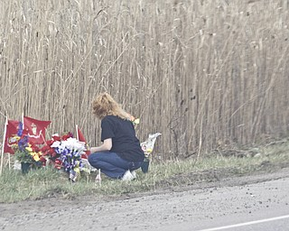 LISA-ANN ISHIHARA   THE VINDICATOR -- Mourner lays flowers at the site of the fatal crash that took the lives of 3 marine recruits last week