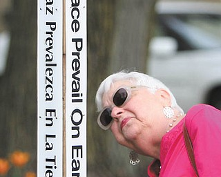 Mary Lou Finesilver reads the various languages on the Peace Pole outside Boardman Center Middle School, Market Street. The memorial pole was dedicated in a Wednesday morning service to Holocaust survivor Bill Vegh, who died in June. Vegh was a frequent speaker to Boardman students about his experience. The ceremony featured a presentation by Eva Schloss, also a Holocaust survivor. After the Holocaust, Schloss's mother married Otto Frank, the father of Anne Frank.