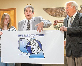 Tom Jacobs, center, and Joe Gleydura, Hubbard Township trustees, unveil the award-winning design of Tori Sylvester, left,  daughter of Tony and Laura Sylvester of Doris Drive, Hubbard, that the township will use on flags. Flags will go to major businesses in the township as a way to thank them for investing in the community. One will fly at the township building.