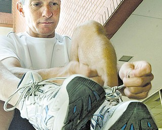 Atty. James Dietz ties his running shoes before training in downtown Youngstown. He is training for his