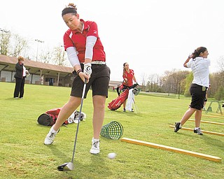 Youngstown State freshman golfer Sarah Heimlich takes a practice swing with her driver. Others at the driving range at Pine Lakes Country Club in Hubbard are junior Katie Rogner, center, and senior Ann Ciavarella.