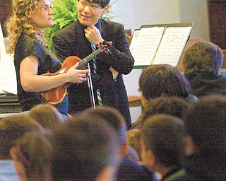 Violinist Jannina Barefield and pianist and director Thomas Osuga, both of the Aurista Chamber Music of New York, get ready to perform for students at St. Joseph's and Immaculate Heart of Mary School in Austintown. They played various pieces from Spanish, black American, Hungarian and Jewish cultures Thursday.