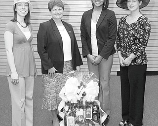 MARK STAHL | THE VINDICATOR: Among the fun-filled events that will take place during a Kentucky Derby party to be sponsored by the Junior League of Youngstown will be a basket raffle and a hat contest. Showing some of the hats that may be seen at the contest and one of the baskets are, from left, Kelly Kiraly, co-chairwoman; Susan Stewart, chairwoman; and Kere Thompson and Marion Dunham, committee members.
