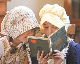 Rachel Wolfe and Katie Masucci read from old school books as second graders from Union Elementary School, Poland, spent Wednesday at the Little Red Schoolhouse on U.S. Route 224 to see how children their age learned many years ago.