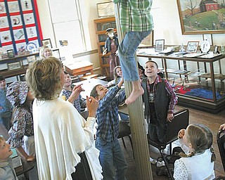 A barefoot Jake Rutana climbs the pole in the Little Red Schoolhouse Wednesday morning as his teacher and classmates cheer him on. Second-graders in Linda Watts' class at Union Elementary School, Poland, spent the day at the schoolhouse on U.S. Route 224.