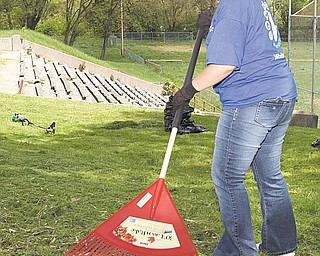 Shauna Desenze, a volunteer from the East Liverpool Walmart, helps clean up the field, long used for sandlot baseball games. Now, the field will be used for flag-football games.