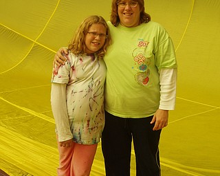 Betsy DeChristofaro and her daughter, Kaila, are standing inside of a hot air balloon that is on the ground.