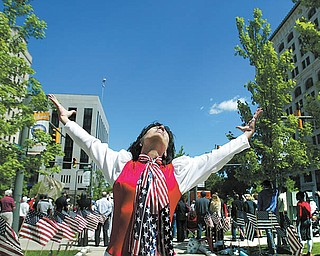 Under sunny, blue skies, Andrea Morvay of Youngstown, dressed in patriotic fashion, dances and prays during the National Day of Prayer observance Thursday in downtown Youngstown. The event ws coordinated by the City Prayer Team of Youngstown. Jonathan Moore, senior pastor at Highway Tabernacle, was keynote speaker.