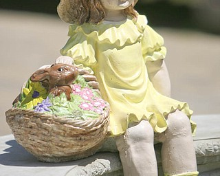 ROBERT K. YOSAY | THE VINDICATOR...Hand painted by the owner Arleen (ok) Fitzer    a litttle girl basket in hand sits on a bench at Farmer Dave's Gift and Garden Shoppe  in  North Lima -- 30-