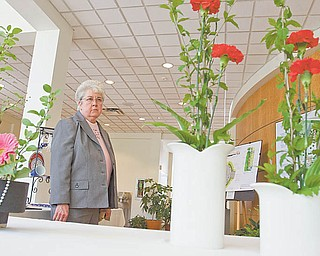 Sister Mary Cunningham of Youngstown looks at floral arrangements Sunday at the Garden Forum Spring Flower Show in Fellows Riverside Gardens in Mill Creek MetroParks. The center also hosted a dahlia show Sunday.
