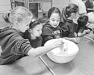 Students in Mrs. Mellony Leonard's second-grade class at St. Patrick School in Hubbard prepare for their First Communion by baking bread for the important day. The bread-making has become a tradition at the school, where these students began the process by mixing the ingredients. Other students shared the mixing, kneading and baking, and at the end of the day, each ate some of the bread, took a loaf home and saved special loaves to present at the communion Mass.