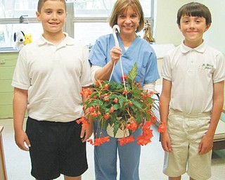 "During Nurse Appreciation Day on May 6, students and staff at St. Patrick School in Hubbard presented a Begonia plant in a hanging basket to the school nurse, Joan Humphry, who is always there to bandage a knee, listen to a problem or give out ""magic mints"" that heal all wounds. Shown during the presentation are, from left, Kent Kyronovich (fifth grade), nurse Humphry, and Julian Maiorano, (fourth grade)."