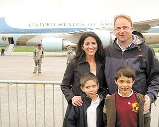 A steel barrier seperates Joe and Judy Kordupel of Boardman, their son Joey, right, and nephew Noah Pecchia, left, from Air Force One along the tarmac at the Youngstown Air Reseve Station in Vienna. The family eagerly awaited a tour on the airplane that brought President Barak Obama to the region to discuss the economy and the V and M Star expansion. Photo by Doug Livingston.